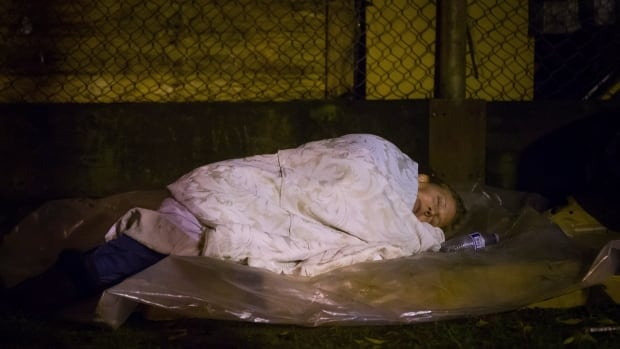 A homeless woman sleeps at a tent city at Oppenheimer Park in the Downtown Eastside of Vancouver.
