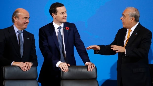 Organization for Economic Co-operation and Development secretary general Angel Gurria, right, talks to British Chancellor of the Exchequer George Osborne, centre, and Spanish Finance Minister Luis de Guindos, left, prior to a ceremony to sign the tax pact.
