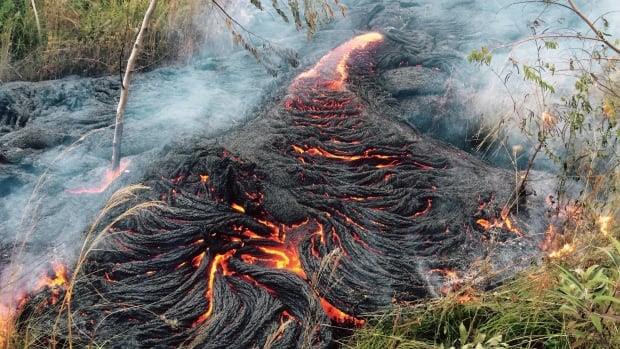 Lava flow burns vegetation near the town of Pahoa on the Big Island of Hawaii. The Kilauea volcano's lava is making a slow crawl toward a major road and threatens to isolate the community.