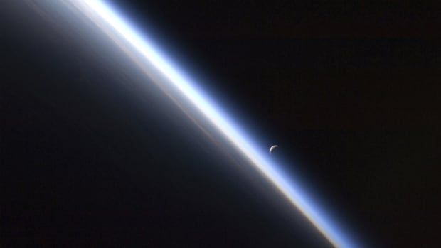 This view of a setting last quarter crescent moon and the thin line of the Earth's atmosphere is one some private sector moguls want to see in person in their lifetime, and they have their fortune to spend trying to get it.