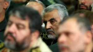 In this Tuesday, Sept. 17, 2013 file photo released by an official website of the office of the Iranian supreme leader, then chief of the Quds Force of Iran's Revolutionary Guard, Ghasem Soleimani, is seen in focus in the background of a meeting of the commanders of the Revolutionary Guard with Supreme Leader Ayatollah Ali Khamenei in Tehran.