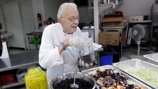 Homeless advocate Arnold Abbott, 90, prepares a salad in the kitchen of The Sanctuary Church on Wednesday in Fort Lauderdale, Fla. Abbott was recently arrested along with two pastors for feeding the homeless in a park.