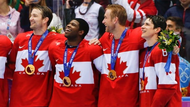 Players from the team Canada men's hockey team pose with their gold medals following a win against the U.S. at the 2014 Winter Olympics in Sochi.