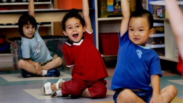 Children put up their hands for ice cream at a daycare centre in Montreal. The availability of daycare improves as children get older, a study by the Centre for Policy Alternatives say.
