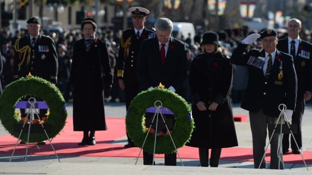 Prime Minister Stephen Harper, centre, and his wife Laureen, right, bow their heads during a Remembrance Day ceremony at the National War Memorial in Ottawa on Tuesday. Princess Anne and Gov. Gen. David Johnston are at left.