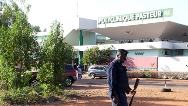A police officer stands in front of the quarantined Pasteur clinic in Bamako, Mali, on Wednesday. The government called for calm as it confirmed that a Guinean patient thought to have brought Ebola into Mali and a 25-year-old Malian nurse who treated him, confirmed as having contracted the virus, had died at the clinic, sparking a huge operation to stem the contagion.