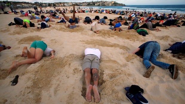 A group of around 400 demonstrators participate in a climate change protest by burying their heads in the sand at Sydney's Bondi Beach Thursday.   It was held ahead of Saturday's G20 summit in Brisbane.