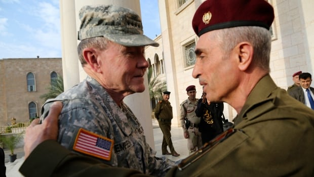Iraq's army chief Gen. Babakir Zebari, right, meets with U.S. Army Gen. Martin Dempsey, left, in Baghdad on Saturday. Dempsey, arrived in Baghdad on an unannounced visit as U.S. commanders prepare to expand American assistance to Iraqi and Kurdish forces battling ISIS.