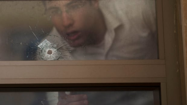 Two youths look at bullet holes and forensic evidence inside a synagogue after a deadly attack in Jerusalem.