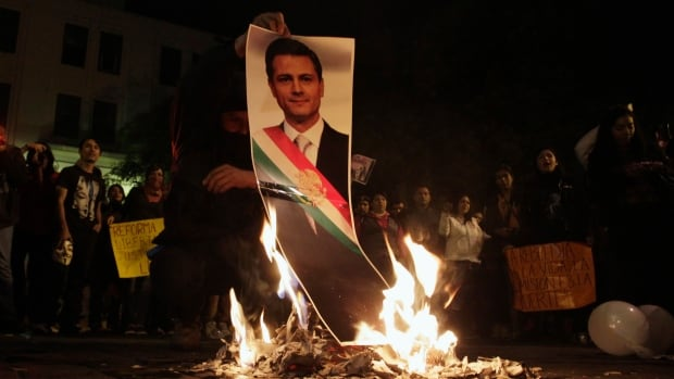 A demonstrator burns a photograph of Mexico's President Enrique Pena Nieto during a protest in support of the 43 missing Ayotzinapa students, in Monterrey on Nov. 20.
