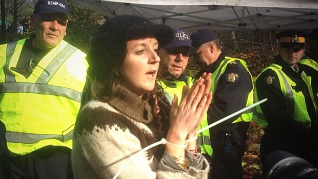 A woman with her wrists zip locked together following her arrest on Saturday tries to exchange information with supporters.