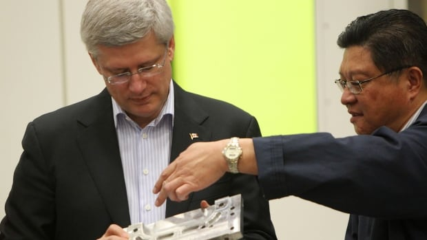 Prime Minister Stephen Harper looks over devices fabricated on 3-D printers at The National Research Council building with employee Lee Xiu in London, Ont., Monday. The NRC facility will share in infrastructure funding announced by Harper.