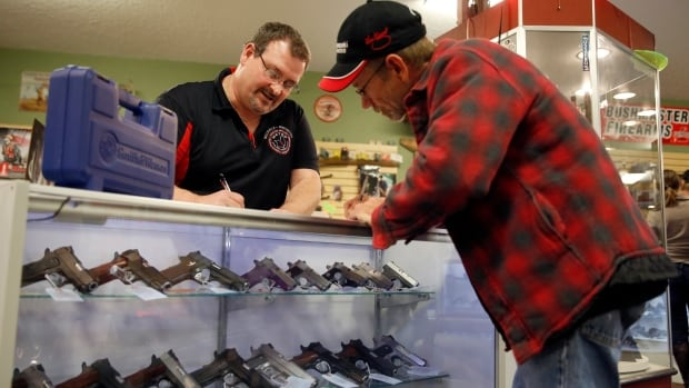 Steven King, left, fills out paperwork while selling a handgun to Dave Benne at Metro Shooting Supplies, in Bridgeton, Mo., on Nov. 15.  Benne, a resident of Florissant, Mo., near Ferguson, said at the time ahead of the grand jury decision on whether to indict police officer Darren Wilson prompted the purchase of his first gun.