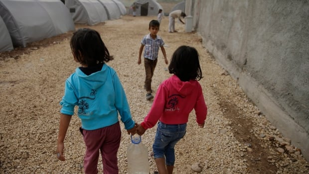 Syrian Kurdish refugees carry water to their tent at a refugee camp near the Turkey-Syria border last month. Auditor General Michael Ferguson's fall 2014 report says that with $200 million earmarked for future aid to Syria, lessons must be learned from past delays.