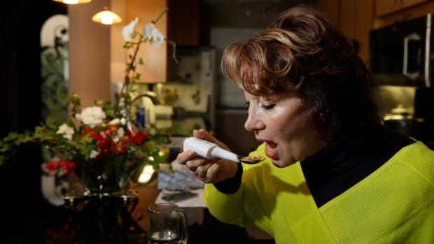 Shirin Vala, 65, who is an essential tremor patient, uses a Liftware Spoon to eat without spilling at her home in Oakland. Google is throwing its support behind the spoon, which senses a shaking hand and make instant adjustments to stay balanced.