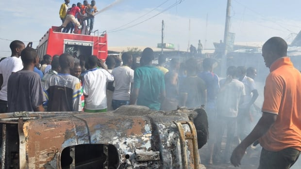 People gather at the scene of a car bomb explosion in Maiduguri, Nigeria, in July. Two teenage girls blew themselves up there Tuesday, killing at least 30 people.