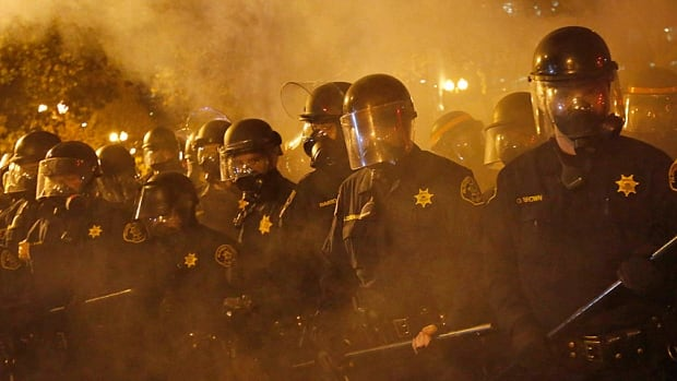 Police officers advance on demonstrators in Oakland, Calif., on Monday night as protests and riots sprung up across the U.S. in the wake of the grand jury decision in the Ferguson, Mo., shooting of Michael Brown.