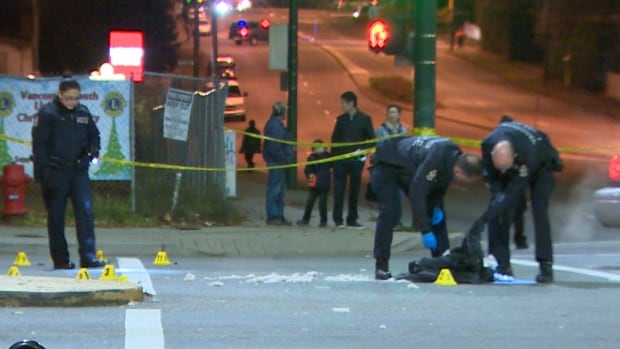 Vancouver police examine clothing left on the street following the shooting of a man in the intersection of Knight Street and E 41st Ave.