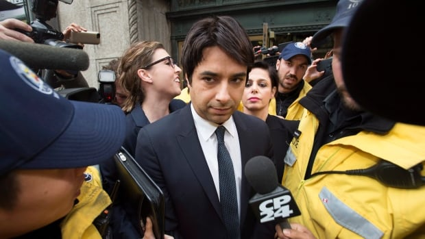 Former CBC Radio host Jian Ghomeshi, centre, is escorted by police out of court past members of the media in Toronto on Nov. 26, 2014.