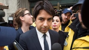 Former CBC Radio host Jian Ghomeshi is escorted by police out of court past members of the media on Nov. 26.  Ghomeshi faces sexual assault charges, but CBC has said none of them is linked to the workplace.