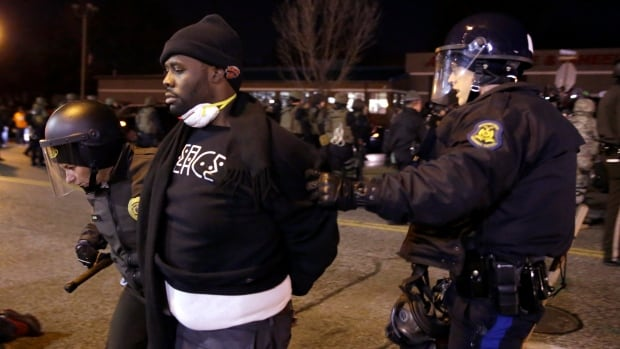Tensions are high in the town. A protester is taken into custody Friday in Ferguson, Mo. during a demonstration outside the police department.