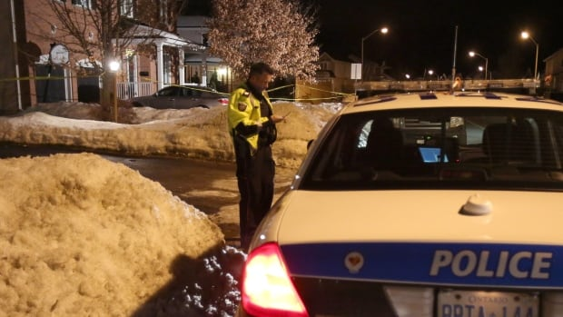 An Ottawa police officer uses his phone at the scene of three deaths in Stittsville, a suburb of Ottawa, in January, 2013. A new report from Statistics Canada says the homicide rate last year was at its lowest since 1966.