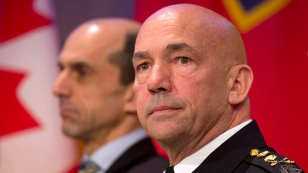 RCMP Commissioner Bob Paulson, right, and Public Safety Minister Steven Blaney listen to a speaker during an announcement on oversight to the organization in Ottawa on Monday. The public-sector integrity commissioner says he found wrongdoing in an investigation into the RCMP's airplane fleet.