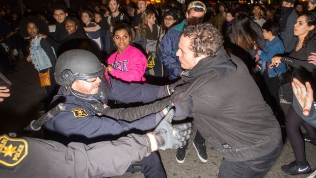 Police officers scuffle with protesters in Berkeley, Calif., where several hundred people took to the streets before being dispersed with tear gas.