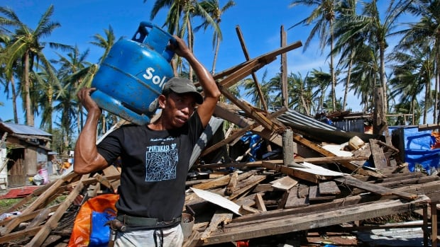 A man carries a gas tank for cooking past a house destroyed by Typhoon Hagupit in central Philippines.  A Waterloo, Ont., company is lending an aerial drone to aid workers to help with the relief efforts after the typhoon.