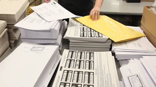 An Elections Canada worker assembles election materials packages in Ottawa in preparation for the next general election. Canadians living abroad who want to vote will have to prove their citizenship and where they last lived in Canada under proposed new rules.