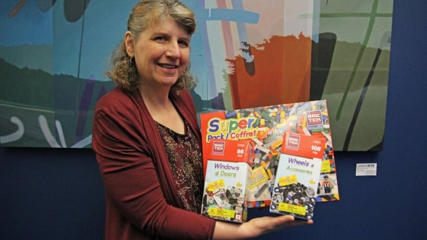 Evelyn Gould is the co-owner of Jester's Fun Factory toy store in Fergus, Ont. She is holding Bric Tek, toy building sets that are alternatives to buying Lego, but still work with Lego sets.