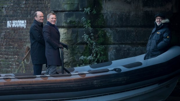 Actors Daniel Craig, center, and Rory Kinnear, left, and director Sam Mendes, right, laugh with onlookers as they film a scene on a canal for the new James Bond movie, SPECTRE, in London, Tuesday.