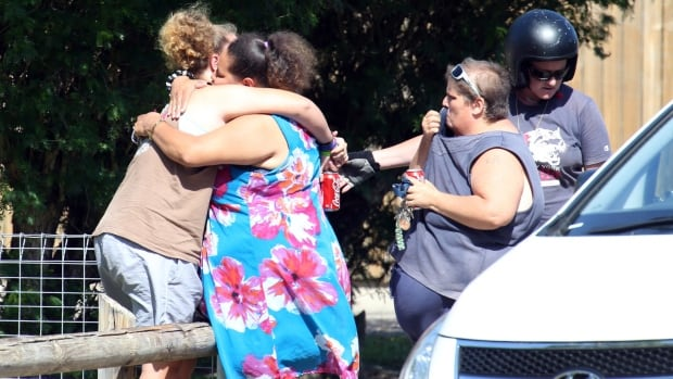 Distraught locals embrace at the scene after eight children, aged between 18 months and 15 years, were found dead in a house in Manoora, near Cairns, Australia on Friday.