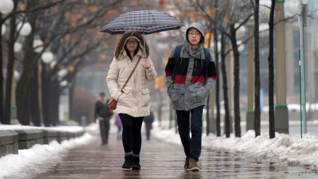 People walk in the rain on Christmas Eve in Ottawa. Similar weather is breaking records in Atlantic Canada on Christmas.