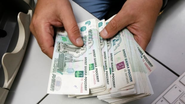 An employee counts Russian ruble banknotes at a private company's office in Krasnoyarsk, Siberia, on Dec. 17. The value of the ruble slipped again Monday following a report the Russian economy contracted for the first time since 2009.