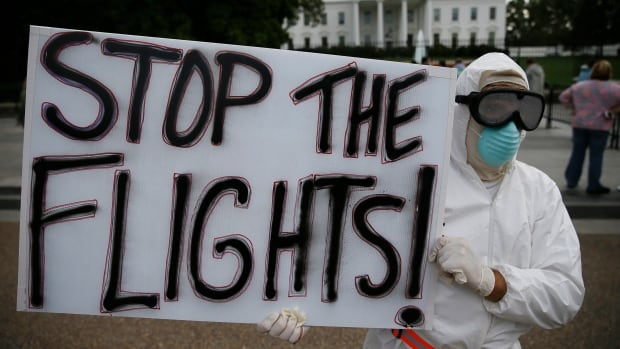 A protester demonstrates in favour of a travel ban to stop the spread of the Ebola virus, in front of the White House in Washington in October. That same month, Canada imposed a travel ban from affected West African countries and subsequently turned away 176 people.
