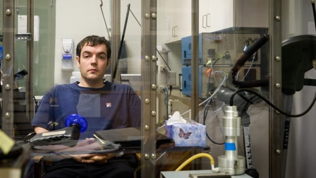 A student participant sits in a special booth at UBC while scientists expose him to diesel exhaust.
