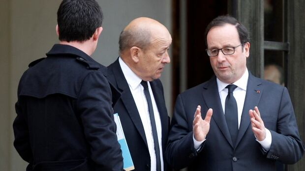 French President François Hollande, right, talks to Defence Minister Jean-Yves Le Drian next to Prime Minister Manuel Valls, as they leave a crisis meeting on Jan. 10 following the attacks in Paris. Hollande's approval ratings increased in the wake of the attacks and hostage-takings that left 20 people dead, including three gunmen.