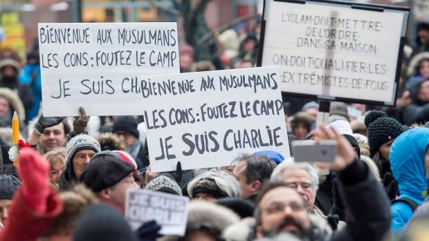 People hold up signs in Montreal, Sunday, January 11, 2015, during a solidarity rally in support of the victims who lost their lives during terror related attacks in France.