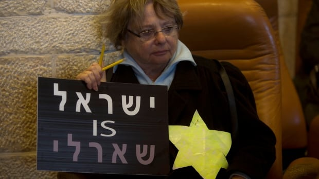 A woman wears a yellow Star of David, like the ones Jews were obligated to wear during World War II, and holds a sign of 'Israel is Charlie' in Jerusalem, Sunday, Jan. 11, 2015.
