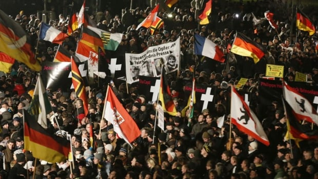 Supporters of anti-immigration movement Patriotic Europeans Against the Islamization of the West (PEGIDA) hold flags during a demonstration in Dresden on Monday.