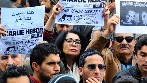 Tunisians hold up old copies of Charlie Hebdo on Bourguiba Avenue in Tunis during a gathering in solidarity with those killed in the attacks. There have been increasing discussions among Muslims who say their community must re-examine their faith to modernize its interpretations and sideline extremists.