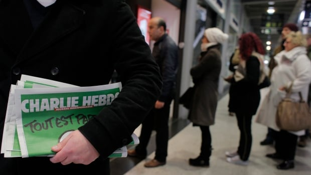 A man leaves after buying Charlie Hebdo newspapers as people queue at a newsstand in Paris on Wednesday.