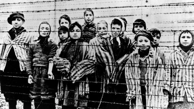 Taken just after the liberation of the Auschwitz-Birkenau Nazi concentration camp by the Soviet army in January 1945, this photo shows a group of children in camp uniform. The girl holding out her arm, showing her ID tattoo, is Miriam Ziegler.