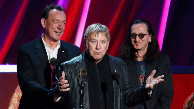 Alex Lifeson, centre, Neil Peart, left, and Geddy Lee of Rush accept the band's induction into the Rock and Roll Hall of Fame in Cleveland in 2013.