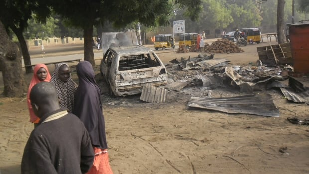 Boko Haram is suspected of using girls as suicide bombers. Children stand near the scene of an explosion in a mobile phone market in Potiskum, Nigeria, Jan. 12. Two female suicide bombers targeted the busy marketplace the previous day.