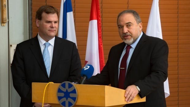 Foreign Affairs Minister John Baird, left, listens as his Israeli counterpart Avigdor Lieberman speaks during their meeting in Jerusalem, Sunday. Baird also met with Palestinian officials.
