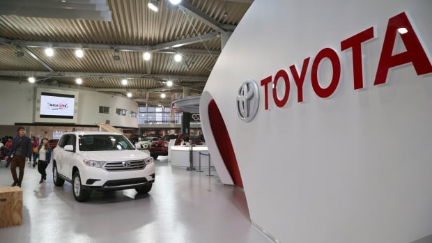 In this Feb. 4, 2014 file photo, visitors inspect cars on display at a Toyota gallery in Tokyo. The Japanese automaker sold 10.23 million vehicles, beating out Volkswagen and General Motors to take the auto industry sales crown for the third straight year.