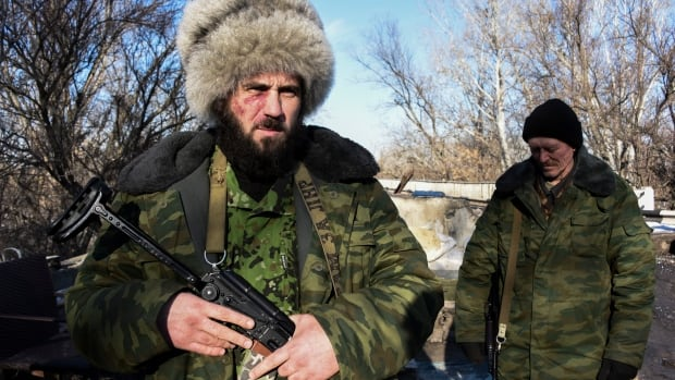 A Russian-backed separatist Cossack stands on guard at the checkpoint north of Luhansk, eastern Ukraine, earlier this year. The German foreign minister says talks on the Russia-Ukraine crisis are 'testing the patience of all involved.'