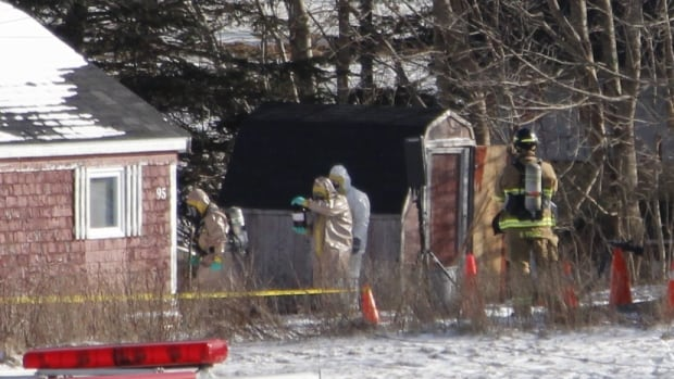 A hazardous materials team removes items from a cottage linked to Christopher Phillips Friday afternoon. Phillips is being held in custody until his next court appearance, scheduled for Thursday.